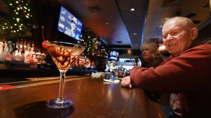 Ken Phillips of Mount Airy looks at a freshly made salted chocolate-covered pretzel martini, a winter-themed drink at Shannon's Saloon at 9338 Baltimore National Pike.