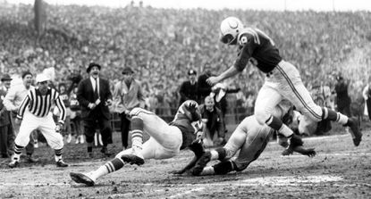 Colts quarterback John Unitas (19) scores a touchdown as Lenny Moore (24) throws a key block on the Giants' Cliff Livingston (89) in the 4th quarter of the 1959 Championship Game, Dec. 27, 1959.