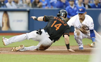 Baltimore Orioles' Noland Reimold advances safely to third just under the tag of Toronto Blue Jays' Josh Donaldson during the fifth inning of a baseball game, Friday, June 10, 2016, in Toronto.