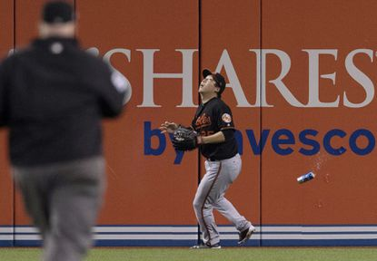 Hyun Soo Kim gets underneath a fly ball as a can falls past him during the seventh inning.