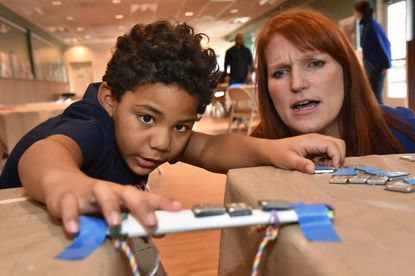 Branson Martin, 6, of Fulton, adds weights to test the sturdiness of the paper bridge he constructed, with coaching by Rebecca Funk, Director of Education at the B&O Railroad Museum. The Bridge to Freedom Workshop highlighted the role of African American bridge builders and railroad workers in securing the Union's victory in the Civil War. The B&O Railroad museum celebrated the Martin Luther King Jr. holiday weekend with programs telling the story of civil rights and the railroad.