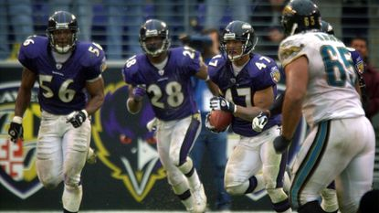 Ravens linebacker Edgerton Hartwell (56) and cornerback Gary Baxter run to protect safety Will Demps (47) as he runs back a game-clinching interception of a pass by Jacksonville Jaguars quarterback Mark Brunell on Oct. 20, 2002. The Ravens won, 17-10.