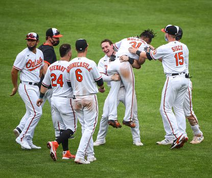 Surrounded by teammates, Baltimore Orioles right fielder Austin Hays (21) lifts up center fielder Cedric Mullins (31) after he hit a sacrifice fly in the 10th inning to score shortstop Ramón Urías (29). The New York Yankees travel to Camden Yards to play the Baltimore Orioles on Thursday, April 29, 2021.