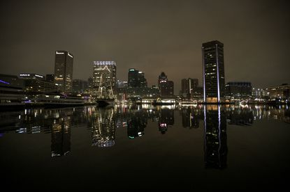 The Baltimore city skyline is reflected in the Inner Harbor before dawn on Thursday.