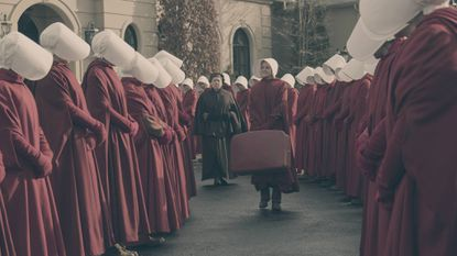Aunt Lydia (Ann Dowd) and Janine (Madeline Brewer) walk down an aisle of Handmaid's as Janine prepares to move to a new assignment.