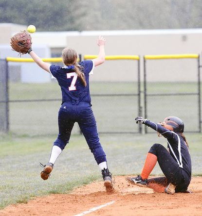 Bel Air's Jennifer Schofield can't reach the ball to make the out as a Rising Sun player slides safetly into third during Wednesday's home game. Rising Sun won, 7-2.