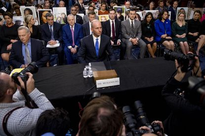Family members of those killed in the Ethiopian Airlines Flight 302 and Lion Air Flight 610 crashes hold photos of their family members behind former Boeing Company President and CEO Dennis Muilenburg (center) as he arrives to testify before a Senate Committee on Commerce, Science, and Transportation hearing on 'Aviation Safety and the Future of Boeing's 737 MAX' on Capitol Hill in October.