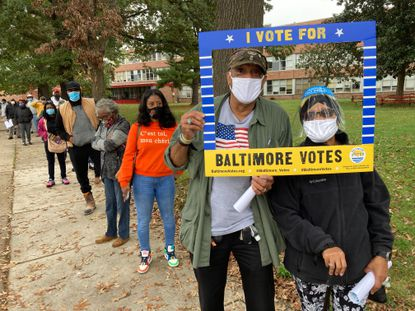 """Clayton and Patricia Price of West Baltimore pose with a frame given to them by a volunteer with """"Baltimore Votes,"""" a non-partisan group, as they wait in line to vote at Edmondson-Westside High School during the first day of early voting on Oct. 26."""