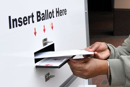 "Two state Senate leaders have called for a ""hybrid"" election to be held in Maryland this fall that would expand the number of in-person voting locations and allow early voting, while still mailing ballots to registered voters across the state. In this June 1, 2020, photo, Leslie Parker Blyther of Baltimore places her ballot in a drop box outside the city's Board of Elections office."
