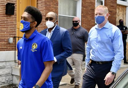 From left, Baltimore Mayor Brandon Scott, Baltimore consent decree monitor Ken Thompson and Brian Nadeau, deputy commissioner for the BPD's public integrity bureau, arrive at the scene of a fatal shooting of a man in the 1800 block of E. Lafayette Avenue last month. (Amy Davis/Baltimore Sun).