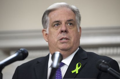 Gov. Larry Hogan, speaking at a JUne news conference, wears a ribbon that symbolizes his fight against cancer.
