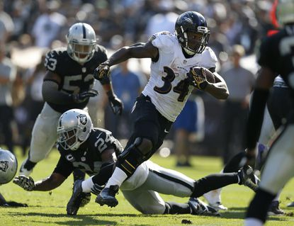The Ravens' Lorenzo Taliaferro runs past the Oakland Raiders' Charles Woodson for a touchdown during the fourth quarter.