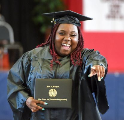 Alternative Education program graduate Tricia Butler George can't hold back her excitement as he and her fellow graduates exit the gym after the Center for Educational Opportunity graduation ceremony Friday in Aberdeen.