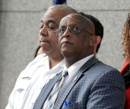 "Baltimore City Police Commissioner Michael Harrison and Mayor Bernard C. ""Jack"" Young listen as City Council President Brandon Scott speaks about the release of the Commissioner's Crime Plan on Thursday, July 18 at police headquarters."