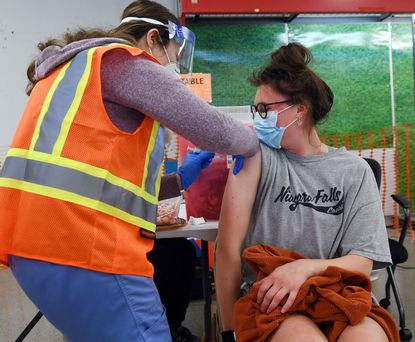 Lexi Ehrman, a senior at Towson University, receives a dose of the Moderna Covid-19 vaccine from Becka Rosenberger, a phlebotomist with the Carroll County Health Department, during a vaccination clinic hosted by the Carroll County Health Department at TownMall of Westminster Thursday, May 6, 2021. The health department had about 250 people scheduled to receive their first dost at Thursday's clinic, which was also taking walk-in patients.