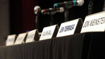 Name cards line a table before a County Council ceremony.