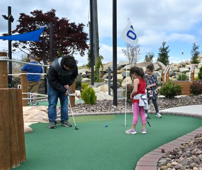 Thad Erich, left, of Fallston takes his shot as his daughters Eloise, front, and Ryan watch closely during a round at Mountain Run mini golf in Fallston.
