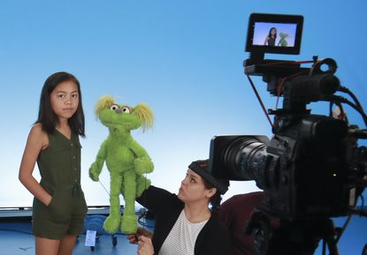 """Salia Woodbury, left, from Irvine, California, appears on the set with """"Sesame Street"""" muppet Karli and puppeteer Haley Jenkins during a 2019 taping about parental addiction. Data show 5.7 million children under 11 live in households with a parent with substance use disorder. Salia's parents are in recovery after struggling with addiction and she shares her experience with the show's Karli, whose muppet character has a mom who is also in recovery."""