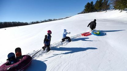 From left, Annie Schinkai, 10, Miranda Moshang, 10, and her father Brant Moshang trudge through deep snow on their way to a sledding hill behind Friendship Valley Elementary School in Westminster Sunday, Jan. 24, 2016.