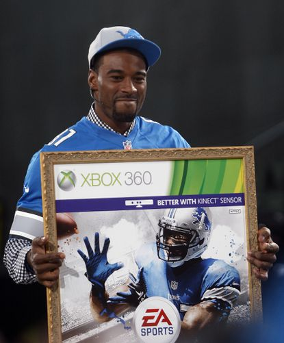 """Detroit Lions receiver Calvin Johnson holds up a poster after being named the cover athlete during the """"Madden NFL 13"""" cover unveiling on the set of SportsNation at Times Square in New York."""