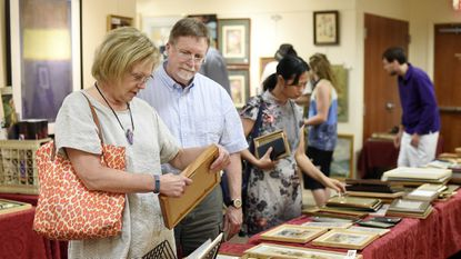 Judy and Tom Reilly browse though pieces displayed for sale during the 2016 yART Sale at the Carroll Arts Center in Westminster. This year's sale is Aug. 18-19.