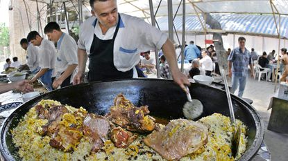 A chef stirs plov, Uzbekistan's national dish, at a cafe owned by Nurshod Asymov in central Tashkent.