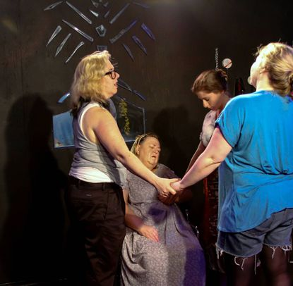 "Three sisters and their mother join for a prayer in a scene from ""Grieving for Genevieve,"" the current production at Venus Theatre in Laurel."