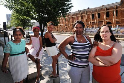 The new, state-of-the-art Hopkins-run school due to open in East Baltimore next year is causing a divide in the community, where parents and other community members say they feel slighted by the school giving last priority to some children in the neighborhood. On site at the school are parents Stephanie Ruffner (right) and Sharon Williams with their children Tara Lowery (left), 7, Faith Spicer, 8, and Nevaeh Donaldon, 10.