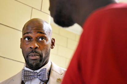 Patterson High School Principal Vance Benton speaks with a student in the hallway.