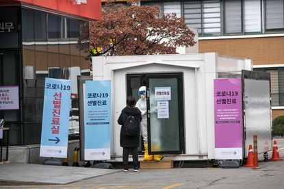A hospital staff member in protective gear speaks to a woman who may be infected with coronavirus at an entrance to the National Medical Center in Seoul, South Korea, on Feb. 26, 2020. The number of new coronavirus infections in South Korea soared on Wednesday, with at least 284 new cases reported.