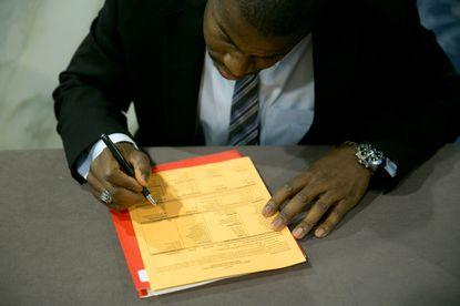 A job seeker fills out a registration card to enter a career fair.