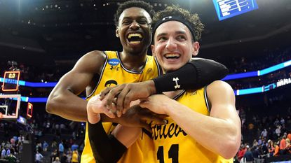K.J. Maura, right, and teammate Jourdan Grant of the UMBC Retrievers celebrate their 74-54 upset victory over the Virginia Cavaliers during the first round of the 2018 NCAA Men's Basketball Tournament on Friday.