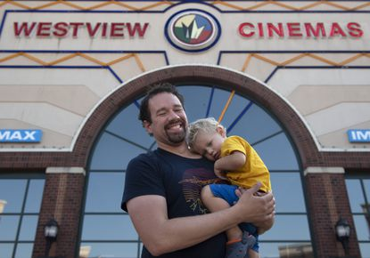 As the liaison between the Frederick, Md., deaf community and Westview Cinemas, Nat Balsley, who is deaf, said that he works to make sure open captioning is accessible to younger generations, like his son, Ryland, who is also deaf. (Graham Cullen/The Frederick News-Post via AP)