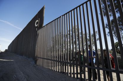 Boys look through an older section of border fence from Mexicali, Mexico, alongside a newly-constructed, taller section, in March 2018. The photographer is standing in Calexico, Calif. File.