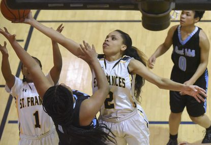 St. Frances' Mia Davis stretches over Pallotti's Tian Addison for a rebound in the second quarterofan IAAM A Conference basketball semifinal in February.