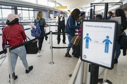 Passengers stand in line at John F. Kennedy International Airport on Oct. 20, 2020, in the Queens borough of New York. New York Gov. Andrew Cuomo announced on Oct. 31 that the state is now requiring travelers from non-neighboring states to test for COVID-19 before and after arrival in the state.