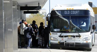 Riders climb onto a MTA bus at the Mondawmin Metro Station, a hub for several MTA bus lines.