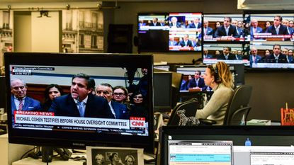 View of television screens inside a newsroom as they air live President Donald Trump's former personal attorney Michael Cohen's testimony before the House Oversight and Reform Committee Wednesday.