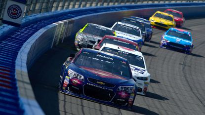 NASCAR driverJimmie Johnson leads a pack of cars going througha turn during the Auto Club 400on Sunday.