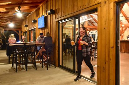 In this October file photo, a bartender carries beers to customers relaxing outdoors at Hopkins Farm Brewery, which opened in July 2020 in Harford County. A workgroup re-examining legislation that allows farm breweries in Harford is considering restrictions for future farm brewery operations that would be among the most restrictive in Maryland.