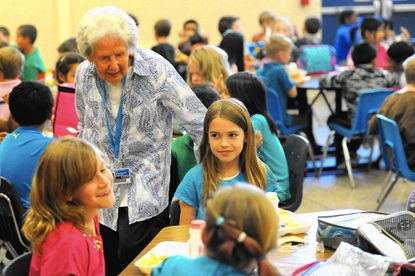 Bertha McManus checks up on third-graders Kya Barrett, left, Nyla Woods and other students at their table during lunch at Halethorpe Elementary School.