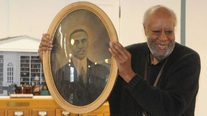 Robert 'Bob' Greene, of Havre de Grace, holds a portrait of his grandfather, William L. Greene, Tuesday as he discusses growing up in Harford County. He was one of several people who talked about local black history at the Historical Society of Harford County in Bel Air.