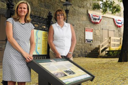 Tiffany Ahalt, left, and Virginia Frank, with the Maryland National Road Association, stand by one of the recently replaced historic panels at the bottom of Main Street in Ellicott City.