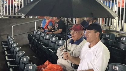 Bel Air residents Carl Conway, left, and Richard Probst sit under an umbrella as they wait through a rain delay for the start of Friday's Aberdeen IronBirds game at Ripken Stadium. The game was ultimately called because of rain.