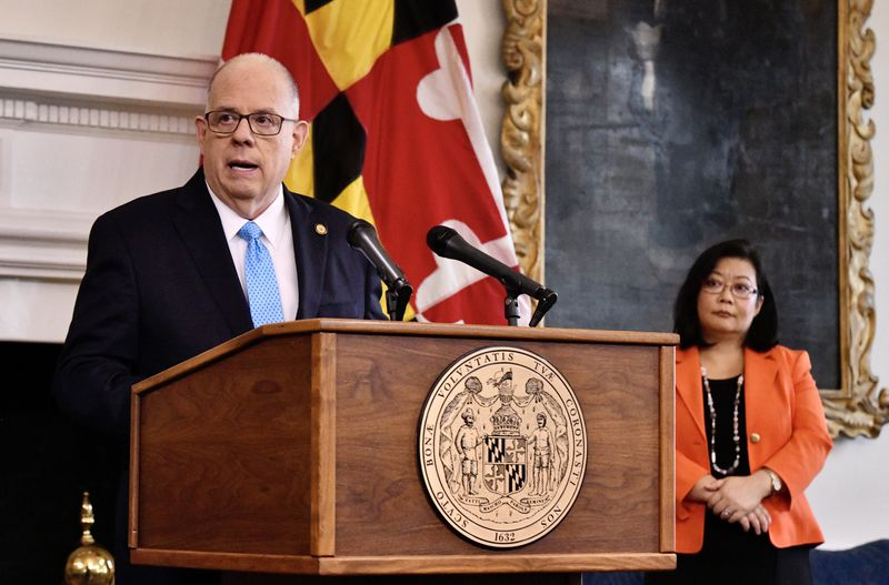 Gov. Larry Hogan announces June 15, 2021, that most of the remaining Maryland COVID-19 restrictions and orders will end July 1. Dr. Jinlene Chan, deputy secretary of public health, stands at right during a news conference at the State House in Annapolis.