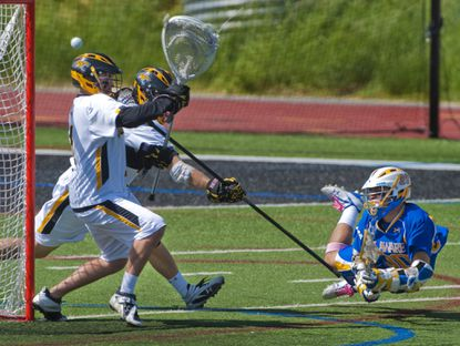 Towson goalkeeper Travis Love stops a shot attempted by Delaware attackman Grant Kaleikau, right, in the 2010 CAA championship game.