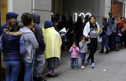 """Hundreds of people overflow onto the sidewalk in a line snaking around the block outside a U.S. immigration office with numerous courtrooms in San Francisco. Santa Clara and San Francisco have filed suit against the Trump administration over its new controversial """"public charge"""" rule that restricts legal immigration. In Maryland, Baltimore and Gaithersburg also challenged the rule in court."""