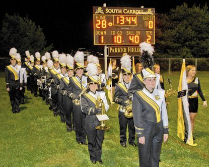 In the early minutes of the second quarter, drum major Emily Crowe, front, gets the Cavaliers Marching Bank in line before marching onto the field at South Carroll High School for the halftime show.