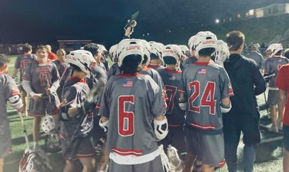 The Glenelg boys lacrosse team holds up the 2A West Region I trophy after defeating Century 16-6 at Centennial High on Friday, June 11, 2021.