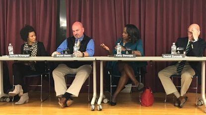 From left, Jamyla Krempel, digital producer for WYPR; Bryan Sears, reporter for the Daily Record; WMAR-2 news anchor Kelly Swoope; and David Zurawik of The Baltimore Sun, sit on a panel about fake news and freedom of press held at the Towson library on Oct. 16.